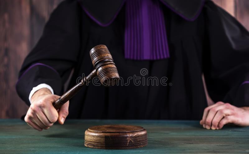 Judge with a wooden judge`s gavel. Supreme Court. Judges gown royalty free stock photo