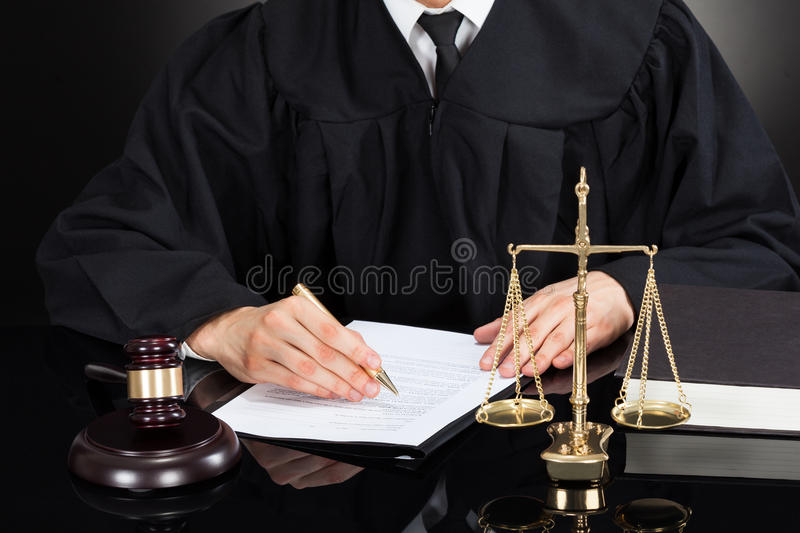 Judge writing on paper at desk royalty free stock photography