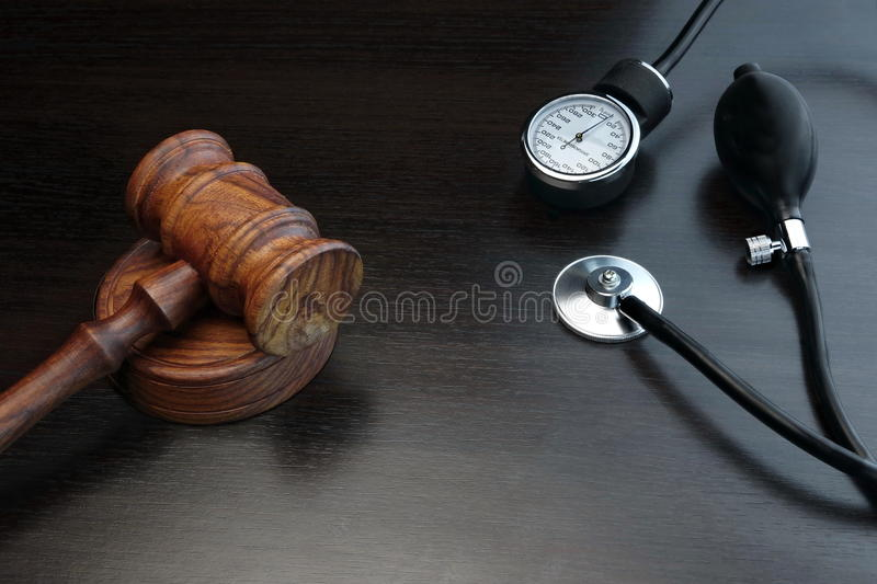 Judges Gavel And Medical Equipment On Black Wooden Background stock photos