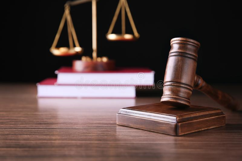 Judges gavel, scales and books on wooden table against black background royalty free stock image