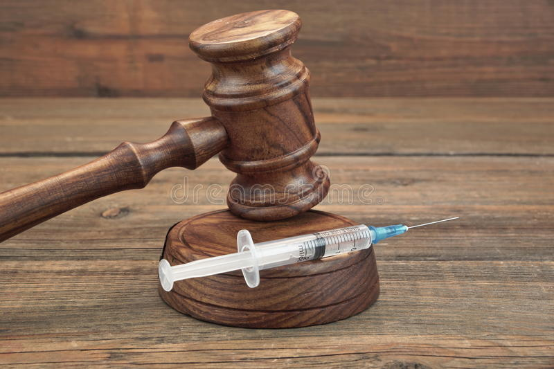 Judges Gavel And Syringe On Brown Wooden Background Close-up. Judges Gavel And Syringe Or Injection On Brown Wooden Table Background Close-up, Front View stock image