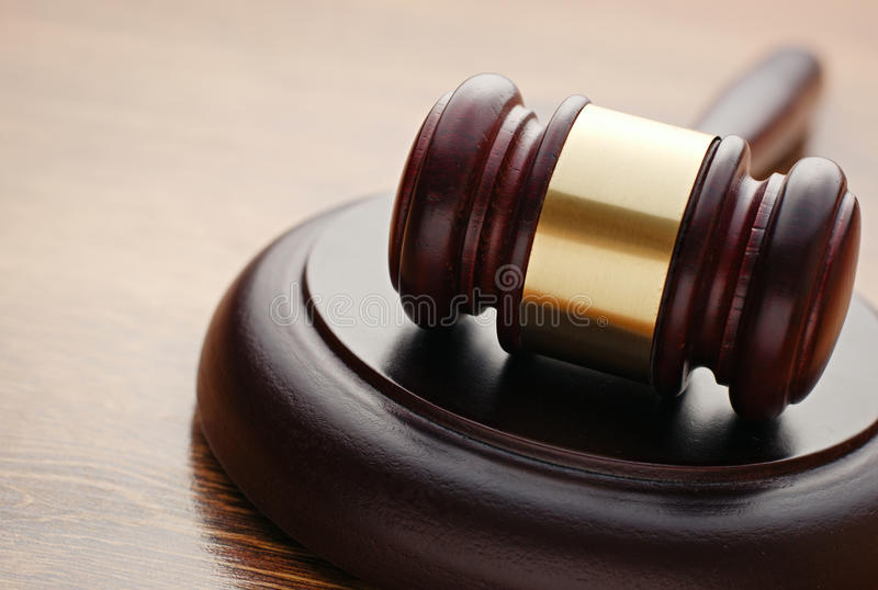 Judges wooden gavel in a courtroom. Lying on its plinth ready to pronounce judgment and sentencing royalty free stock photo