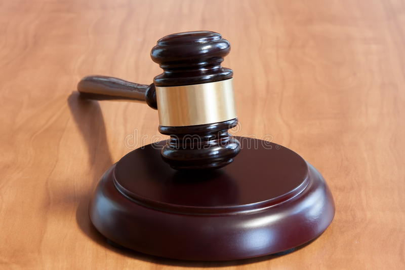 Judicial hammer on a wooden table. Judicial hammer with a support on a wooden table royalty free stock image