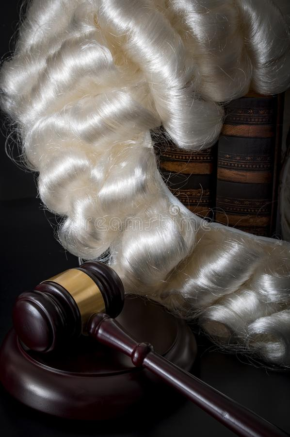 Judicial system and legal code concept with judge powdered wig hanging on old law books next to a judge's wooden gavel or mallet royalty free stock photo