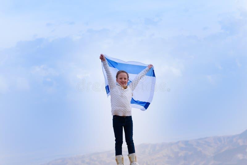 Judisk flicka för liten patriot med flaggan av Israel på bakgrund för blå himmel royaltyfri bild