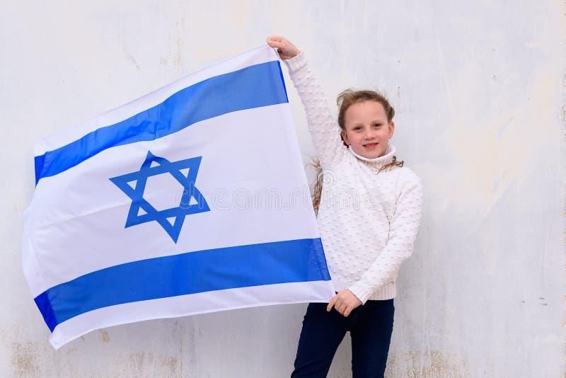 Judisk flicka f?r liten patriot med flaggan Israel p? vit bakgrund royaltyfri bild