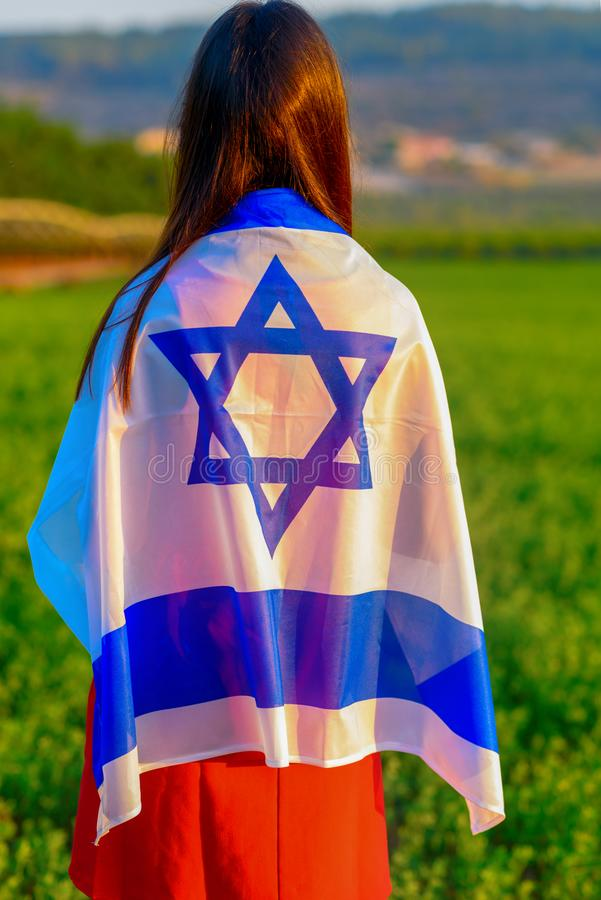 Judisk flicka med flaggan av Israel p? att f?rbluffa landskap i h?rlig sommar arkivfoto