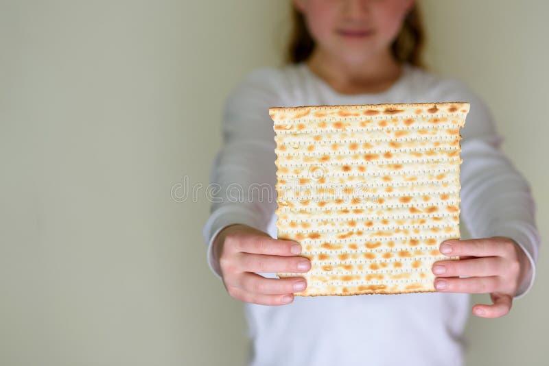 Judisk flickainnehavmatzah f?r p?skh?gtid royaltyfri foto