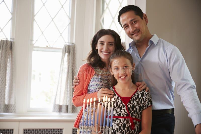 Judiska föräldrar och le för dotter som tänds stearinljus på menoror royaltyfria foton