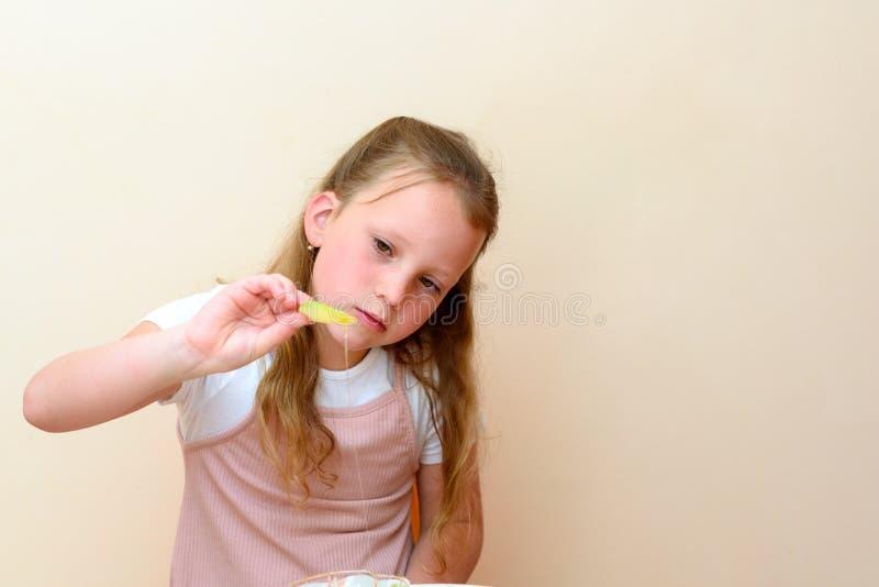 Judiskt barn som doppar äppleskivor in i honung på Rosh HaShanah royaltyfri foto