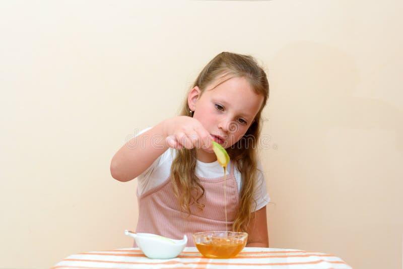 Judiskt barn som doppar äppleskivor in i honung på Rosh HaShanah royaltyfria bilder