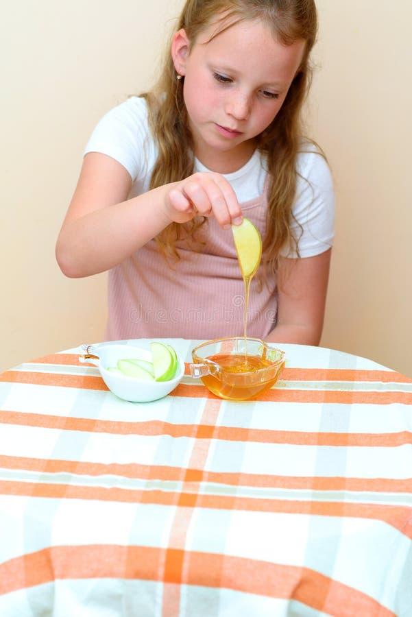 Judiskt barn som doppar äppleskivor in i honung på Rosh HaShanah arkivfoto