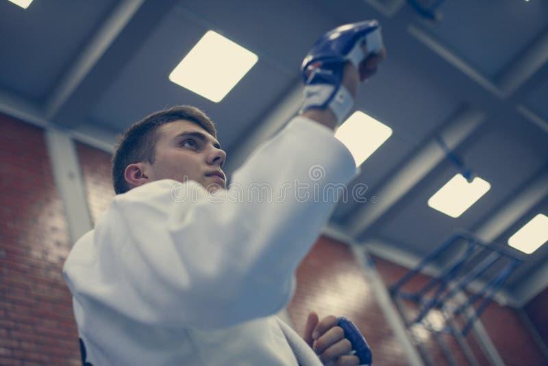 Judo de pratique de mâle dans le kimono avec le gant de combat photographie stock libre de droits