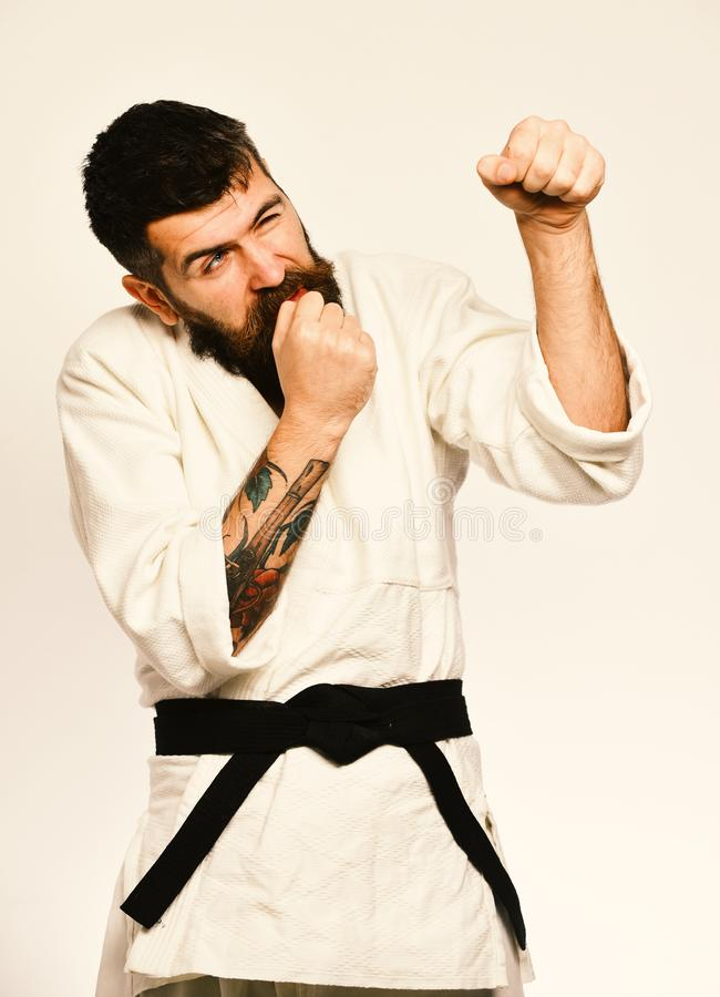 Judo master with black belt bites nails in fear. And gives unsure punch. Karate man with uncertain face in uniform. Man with beard in white kimono on white stock image