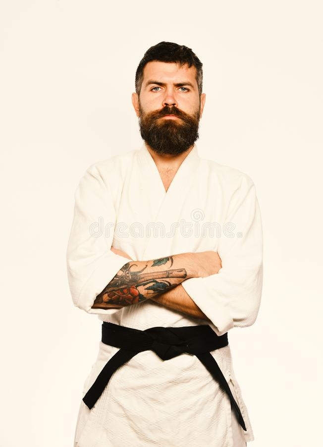 Judo master with black belt holds arms crossed. Man with beard in white kimono on white background. Karate man with serious face in uniform. Japanese martial royalty free stock photo