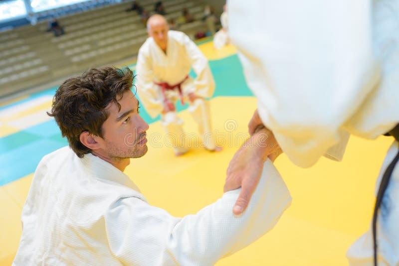 Judoka ajudou pelo amigo a levantar-se após a derrota imagem de stock