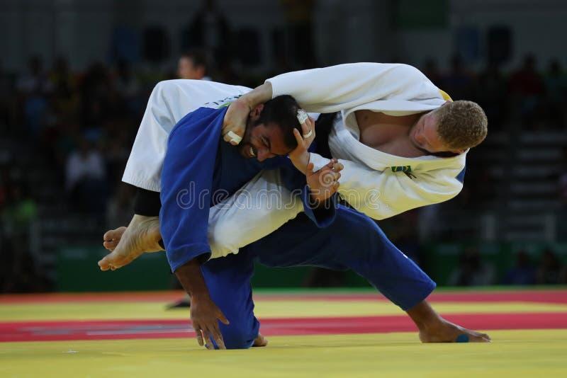 Judoka Rafael Buzacarini de Brasil no branco na ação contra Pablo Aprahamian de Uruguai durante durante o fósforo dos homens -100 fotos de stock royalty free