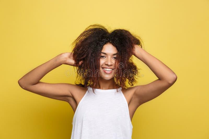 Juego afroamericano atractivo hermoso de la fijación de la mujer con su pelo afro rizado Fondo amarillo del estudio Copie el espa imagenes de archivo