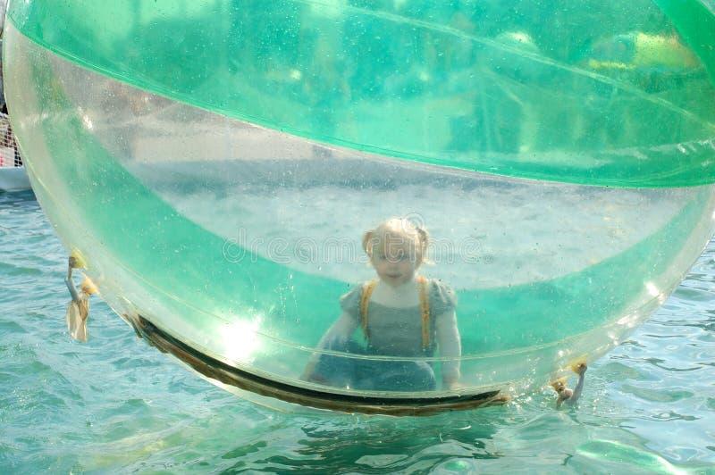 Juego bonito de la niña en la bola inflable. fotos de archivo