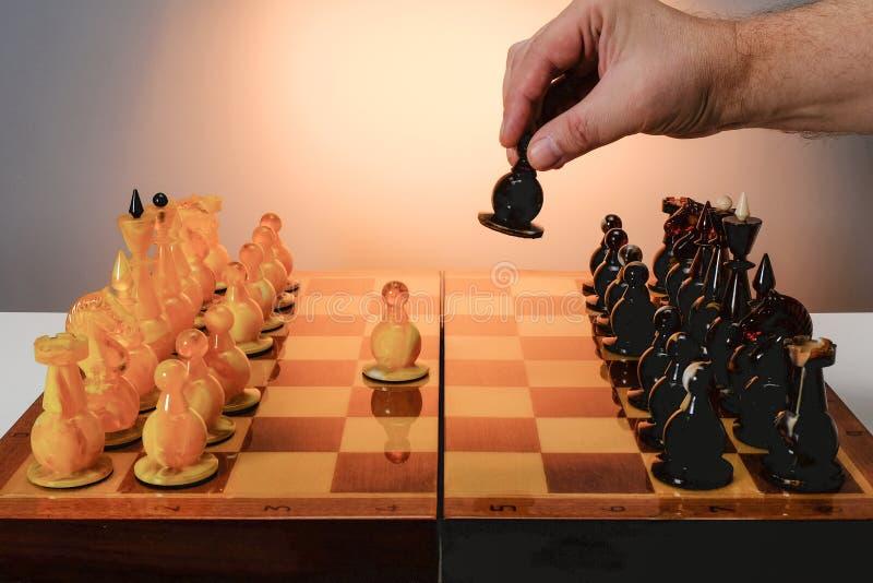 Juego de ajedrez con los pedazos de ajedrez ambarinos en el tablero Mano del jugador que sostiene el empe?o negro Con el fondo de fotografía de archivo