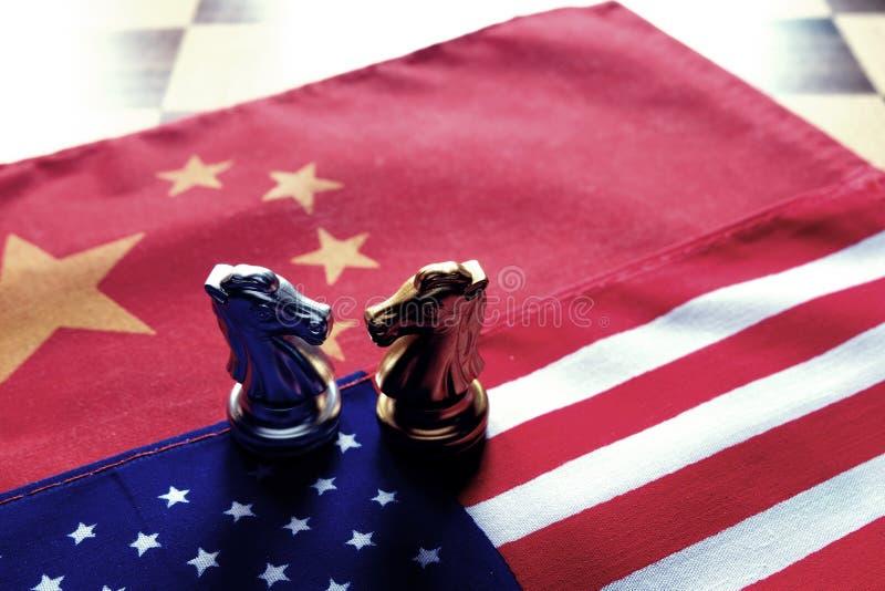 Juego de ajedrez Dos caballeros cara a cara en banderas nacionales chinas y americanas Guerra comercial y conflicto entre dos paí fotos de archivo