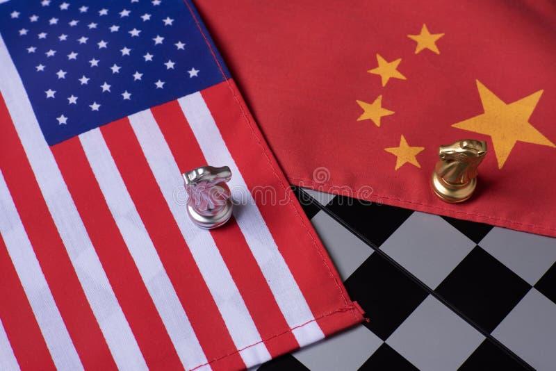 Juego de ajedrez, dos caballeros cara a cara en China y banderas nacionales de los E.E.U.U. Concepto de la guerra comercial Confl fotografía de archivo libre de regalías