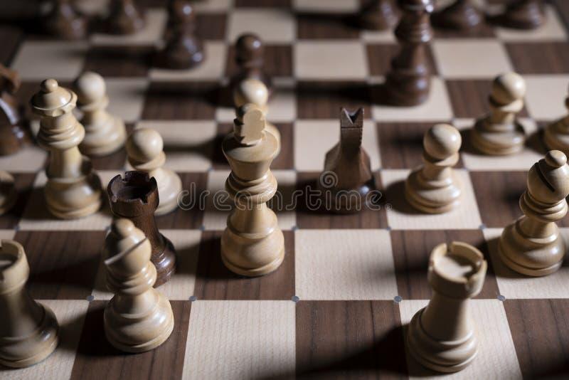 Juego de ajedrez Los pedazos blancos y negros están luchando para la victoria La figura central está en foco imágenes de archivo libres de regalías