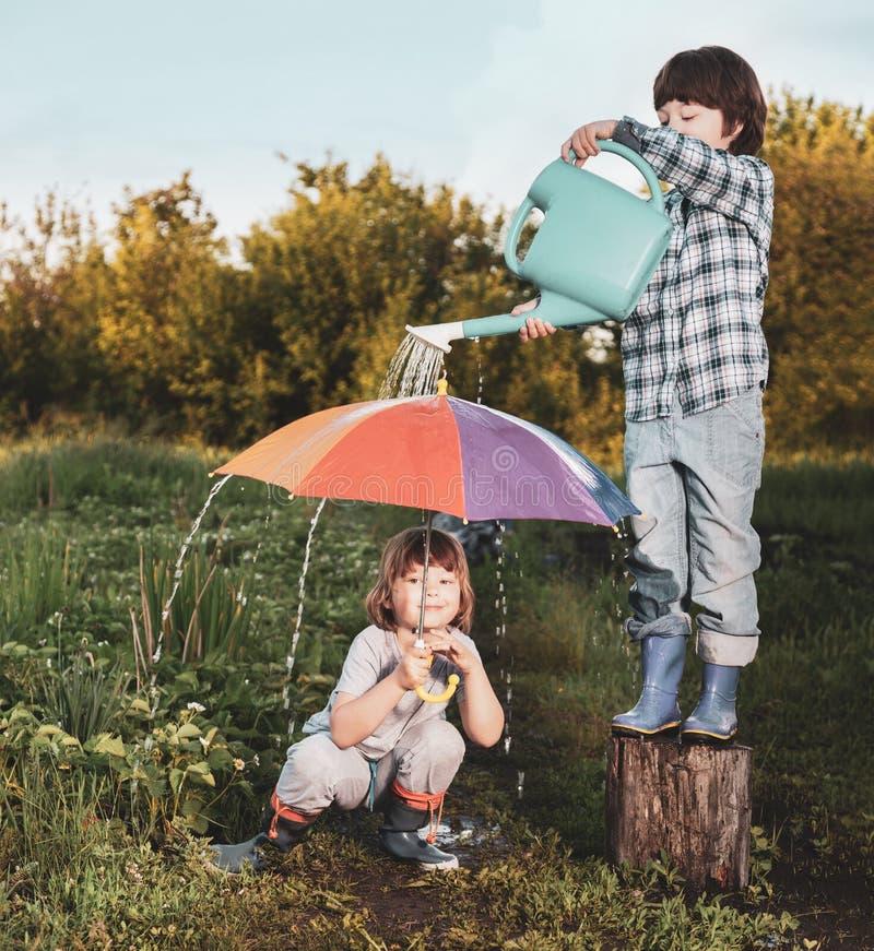 Juego de dos hermanos en lluvia al aire libre imágenes de archivo libres de regalías