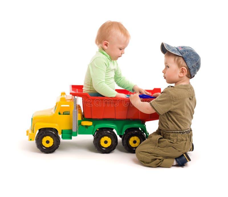 Juego de dos niños pequeños con el carro del juguete foto de archivo libre de regalías