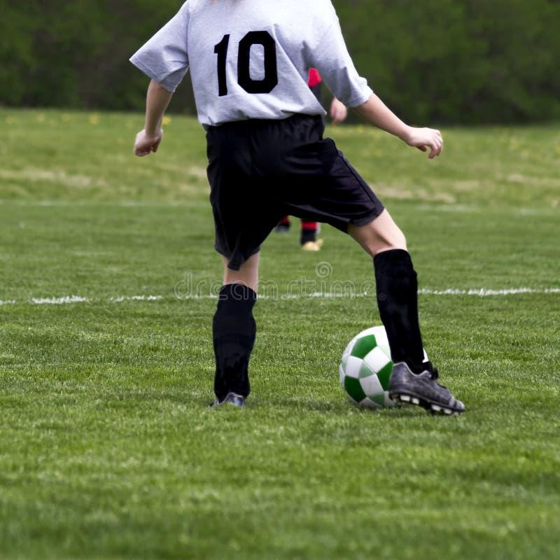 Juego de fútbol de los muchachos imagen de archivo