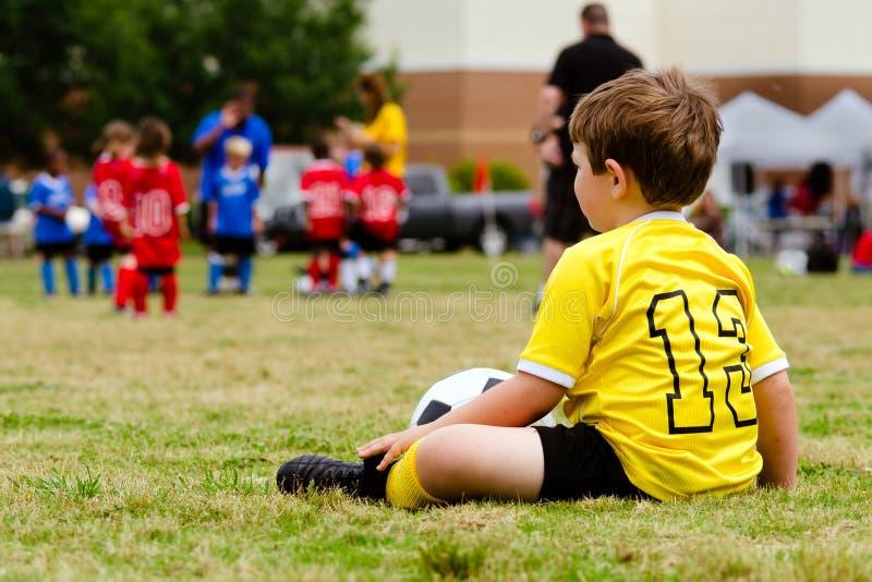 Juego de fútbol de observación de la juventud del niño imagenes de archivo