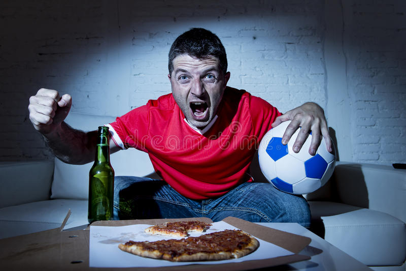 Juego de fútbol de observación del hombre fanático del fanático del fútbol en la celebración de la TV imágenes de archivo libres de regalías