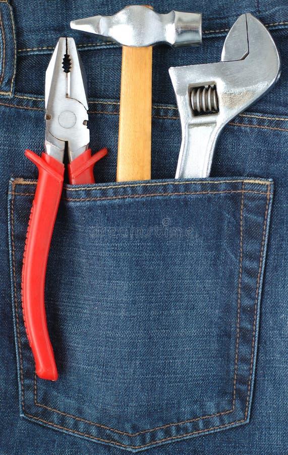 Juego de herramientas en bolsillo de los pantalones vaqueros fotografía de archivo libre de regalías