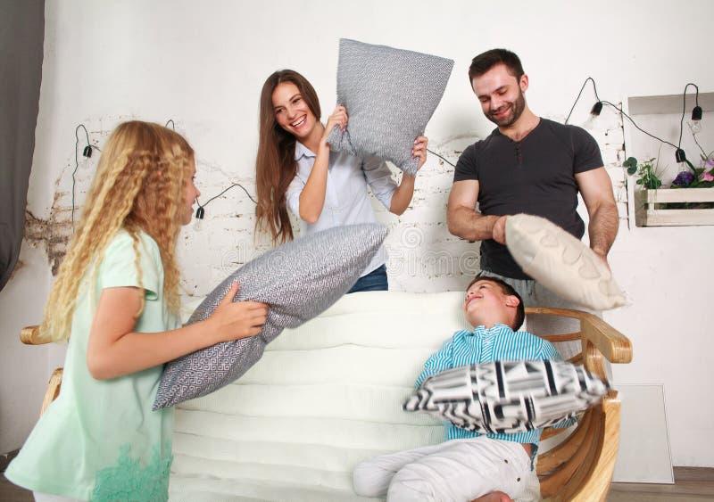 Juego de la familia joven y de dos niños en casa que lucha con las almohadas fotos de archivo