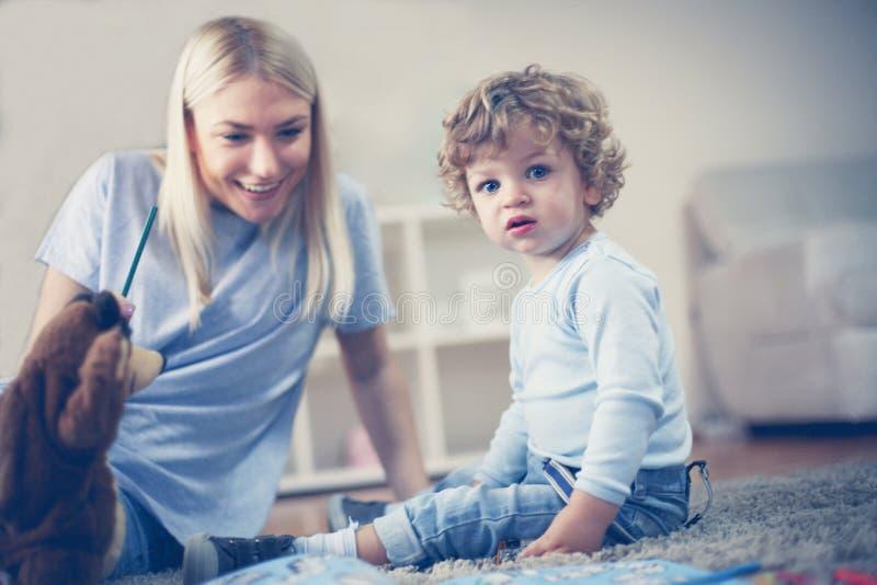 Juego de la madre con el hijo en sala de estar foto de archivo