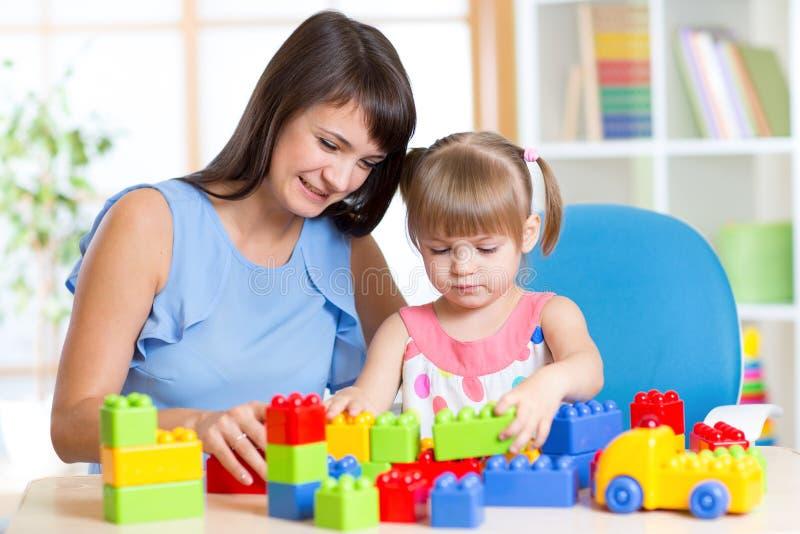 Juego de la madre y del niño con los juguetes en casa foto de archivo