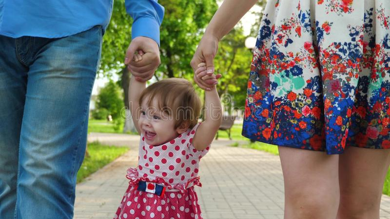 Juego de la mamá y del papá con el bebé del aumento del bebé por las manos para arriba, la niña que salta y que ríe, paseo de la  imágenes de archivo libres de regalías