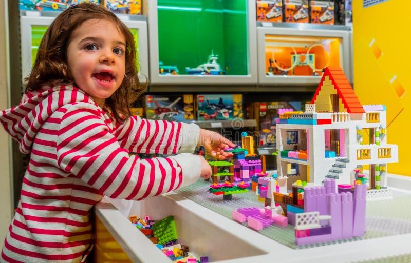 Juego de la muchacha del niño del bebé con los ladrillos de Lego dentro de Lego Store foto de archivo