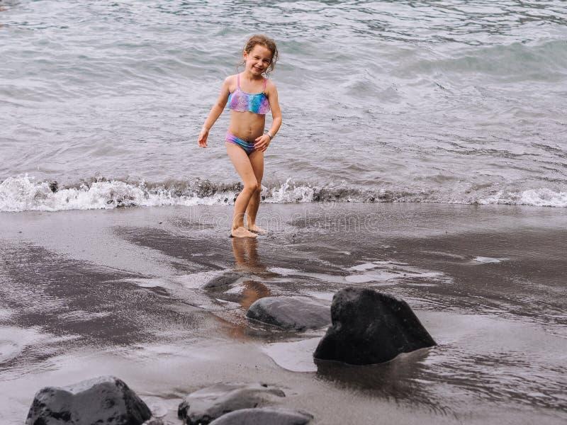 Juego de la muchacha en una playa en las ondas del mar y el jugar en la playa volcánica de la arena fotografía de archivo