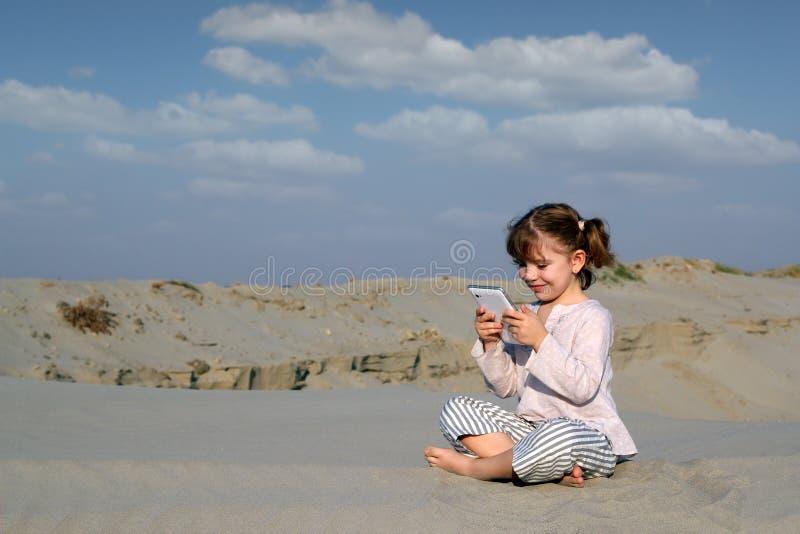 Juego de la niña con PC de la tablilla en desierto fotos de archivo