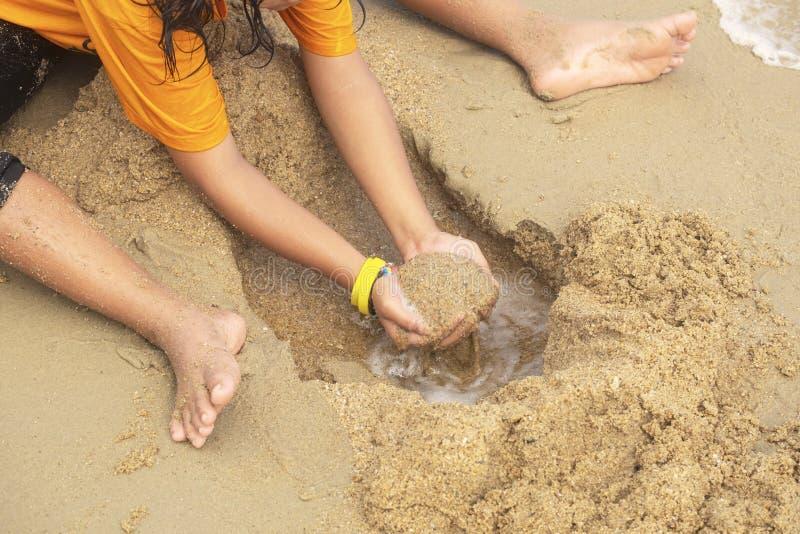 Juego de la niña que cava una arena mojada en la playa y el mar foto de archivo libre de regalías