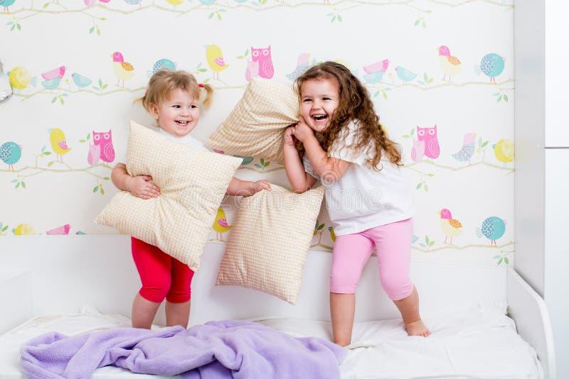 Juego de las hermanas de los niños en la cama dentro foto de archivo