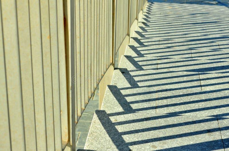 Juego de las sombras entre la verja y las escaleras en la ciudad fotografía de archivo