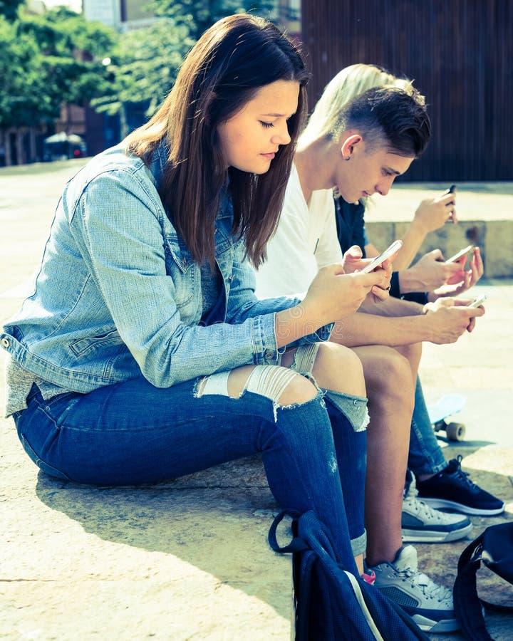 Juego de los adolescentes en smartphones en patio imagen de archivo