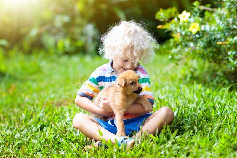 Juego de los niños con el perrito Niños y perro en jardín imágenes de archivo libres de regalías