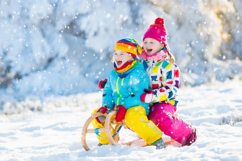Juego de los niños en nieve Paseo del trineo del invierno para los niños imágenes de archivo libres de regalías