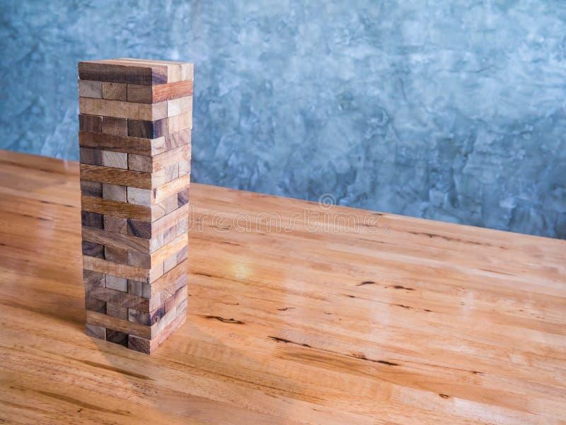 Juego de madera de los bloques o juego del jenga en la tabla de madera con vagos de la pared del cemento fotografía de archivo libre de regalías