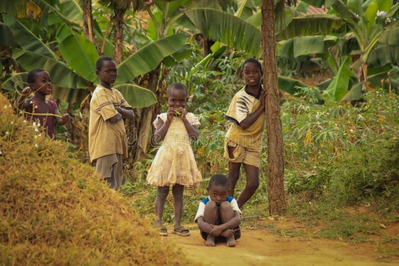 Juego de niños africano del pueblo cerca de sus hogares en el suburbio de Kampala imágenes de archivo libres de regalías