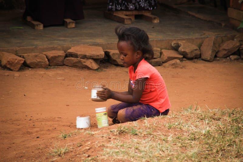 Juego de niños africano del pueblo cerca de sus hogares en el suburbio de Kampala foto de archivo