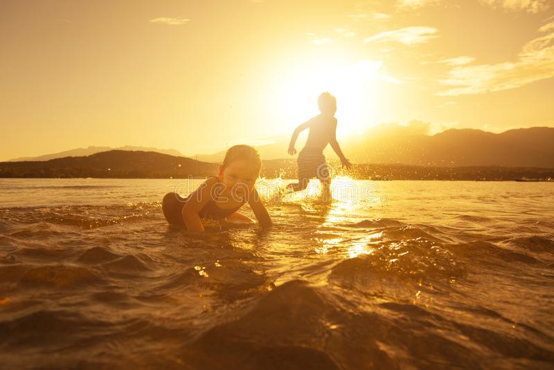 Juego de niños alegre en el mar en la puesta del sol fotos de archivo